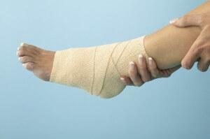 Woman Holding Bandaged Ankle